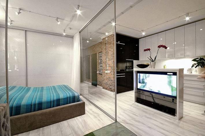 спальня за прозрачной перегородкой в однокомнатной квартире