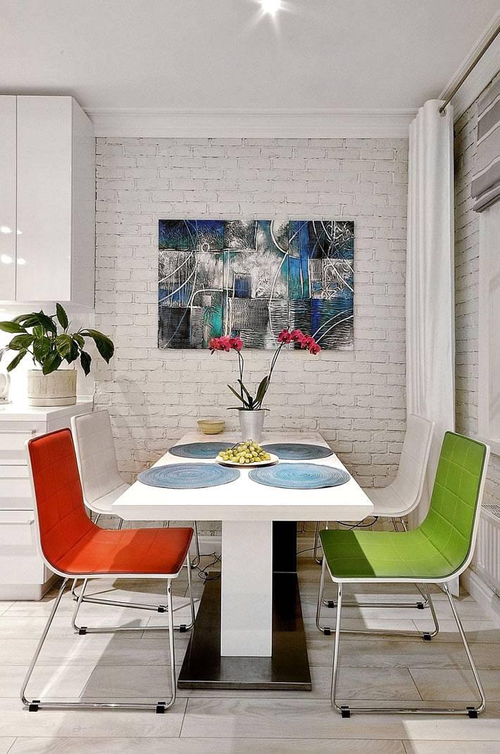 белая кирпичная стена в дизайне столовой зоны с яркими стульями