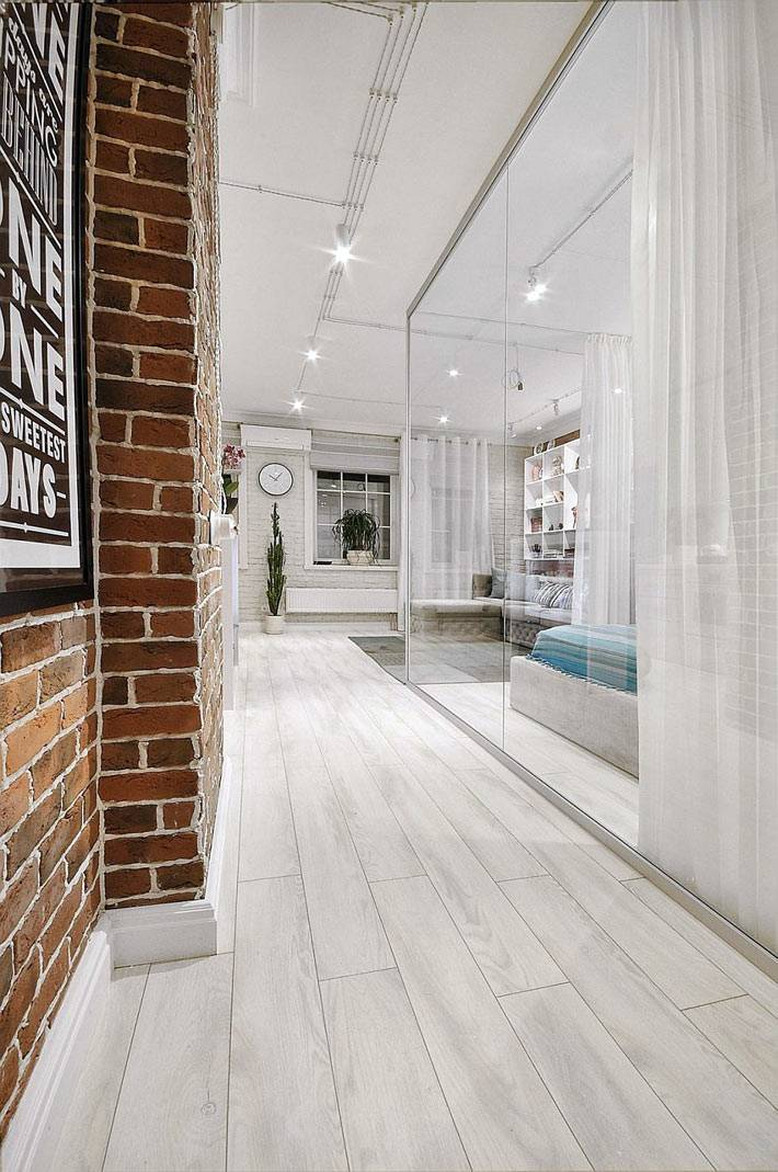 светлый коридор и точечные светильники в интерьере однокомнатной квартиры