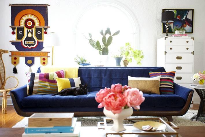 интерьер гостиной комнаты с большим синий диваном