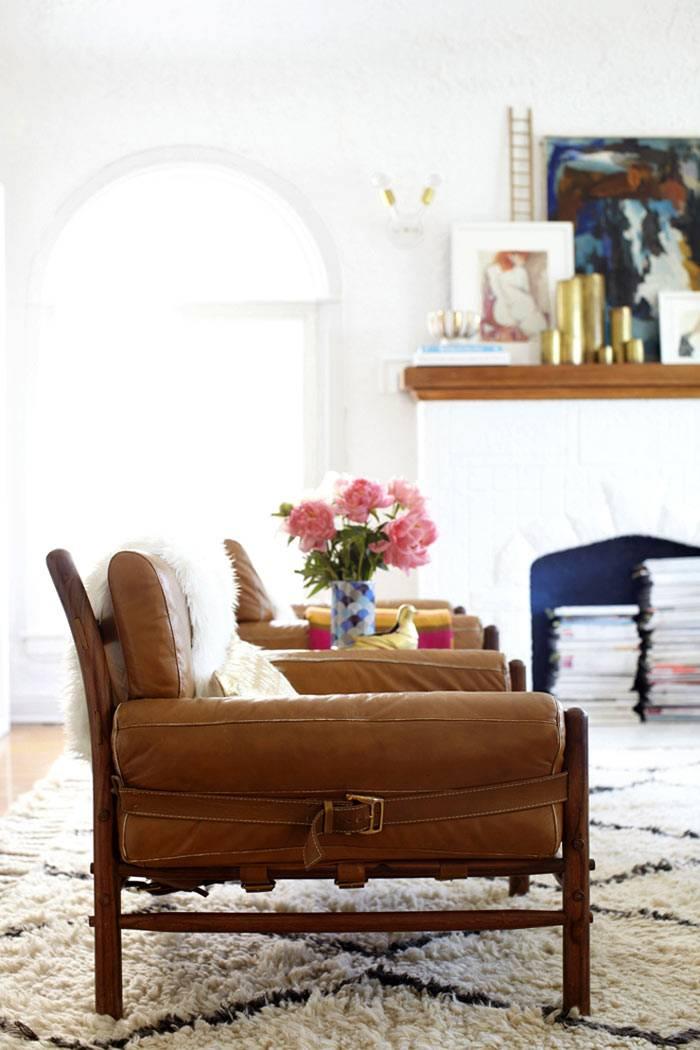 коричневые кожаные кресла и пушистый белый ковер в дизайне гостиной