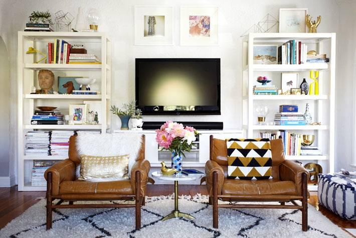 симментричный дизайн интерьера гостиной комнаты с белыми стеллажами