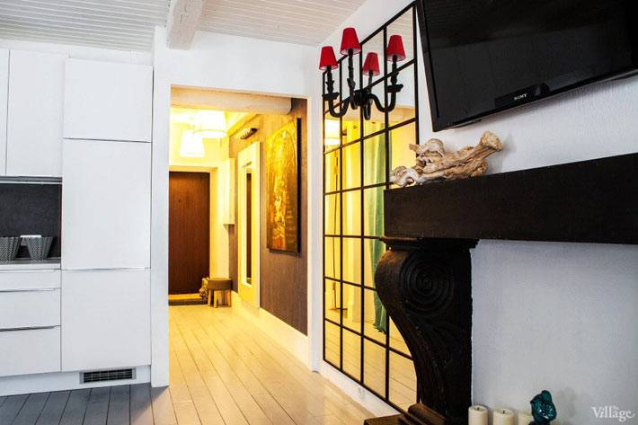 черный фальш-камин в квартире под телевизором