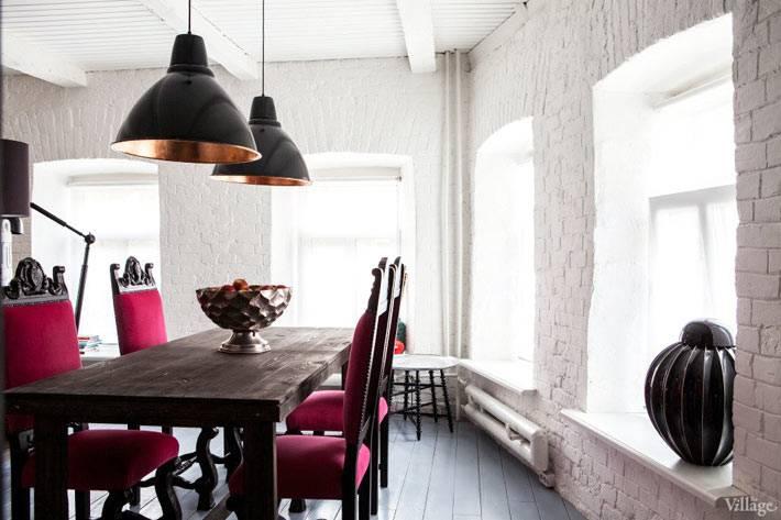 столовая зона с белой кирпичной стеной и черными люстрами