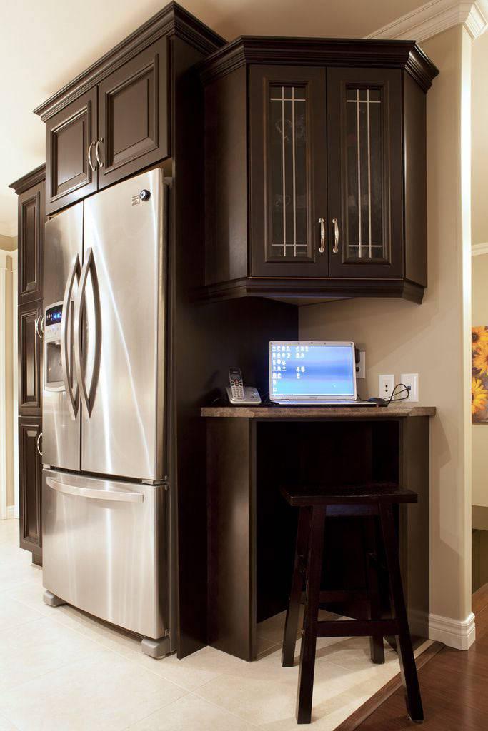 небольшой рабочий угол на кухне с коричневой мебелью