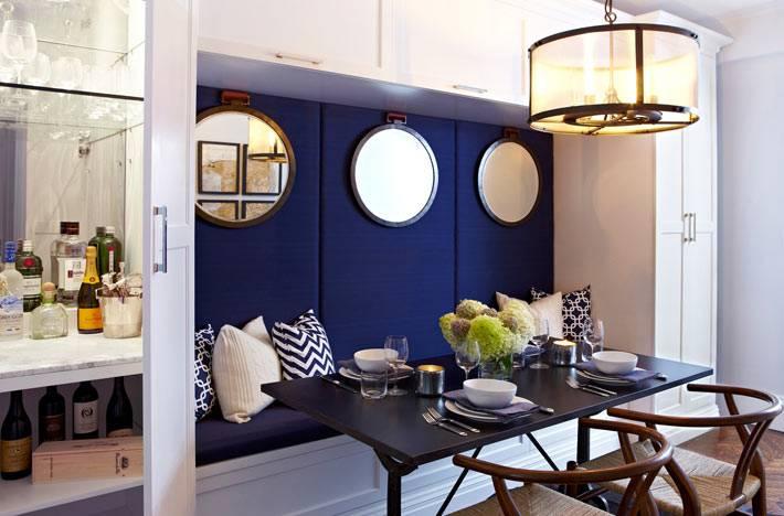 круглые зеркала на синей стене в дизайне столовой комнаты