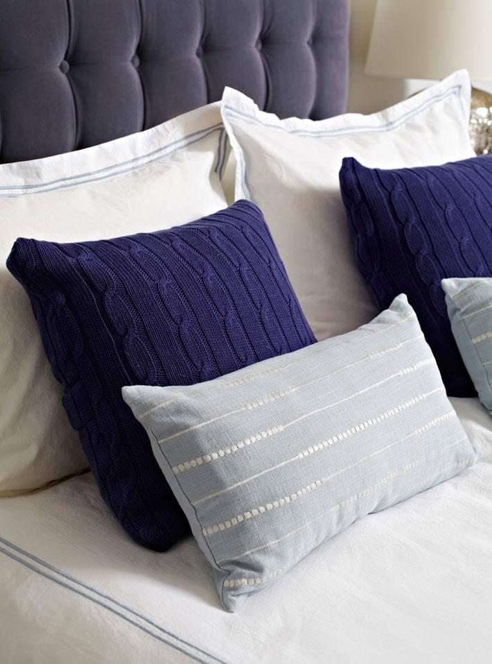 вязанные декоративные подушки на красивой синей кровати фото