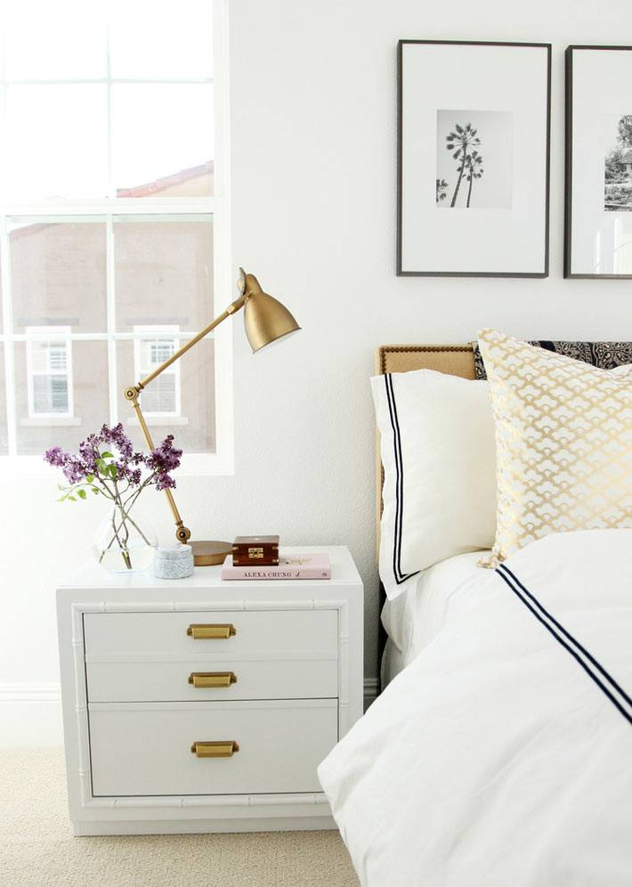 белая прикроватная тумба с латунной лампой в спальне фото