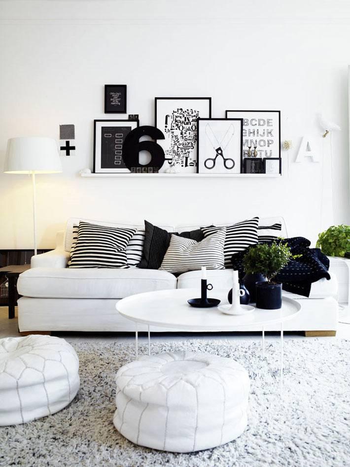 черно-белый интерьер гостиной комнаты с белыми пуфами
