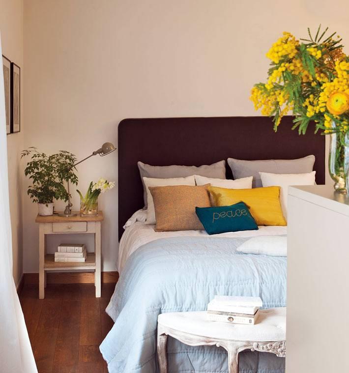 уютная спальня с удобной кроватью и цветами в вазе