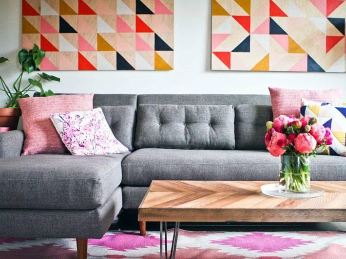 серый диван и яркие картины в интерьере гостиной комнаты