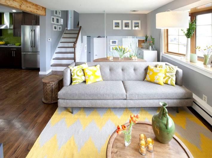 серый диван с желтыми подушками и желтым ковром
