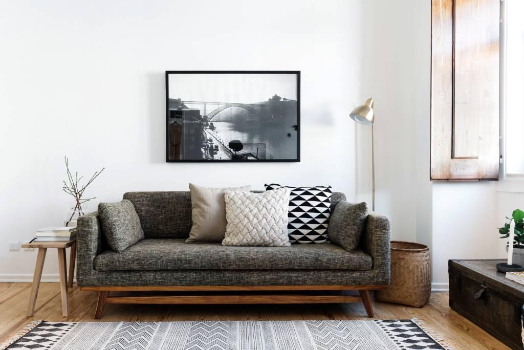 стильный диван в интерьере комнаты с белыми стенами