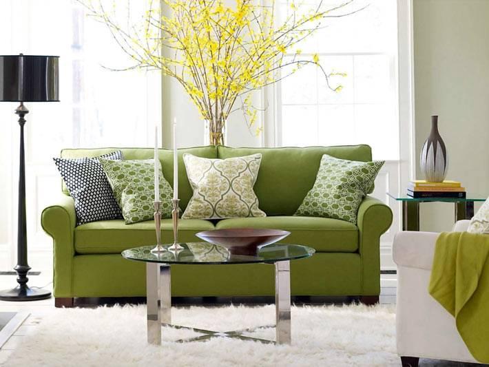 зеленый диван с подушками в интерьере гостиной фото