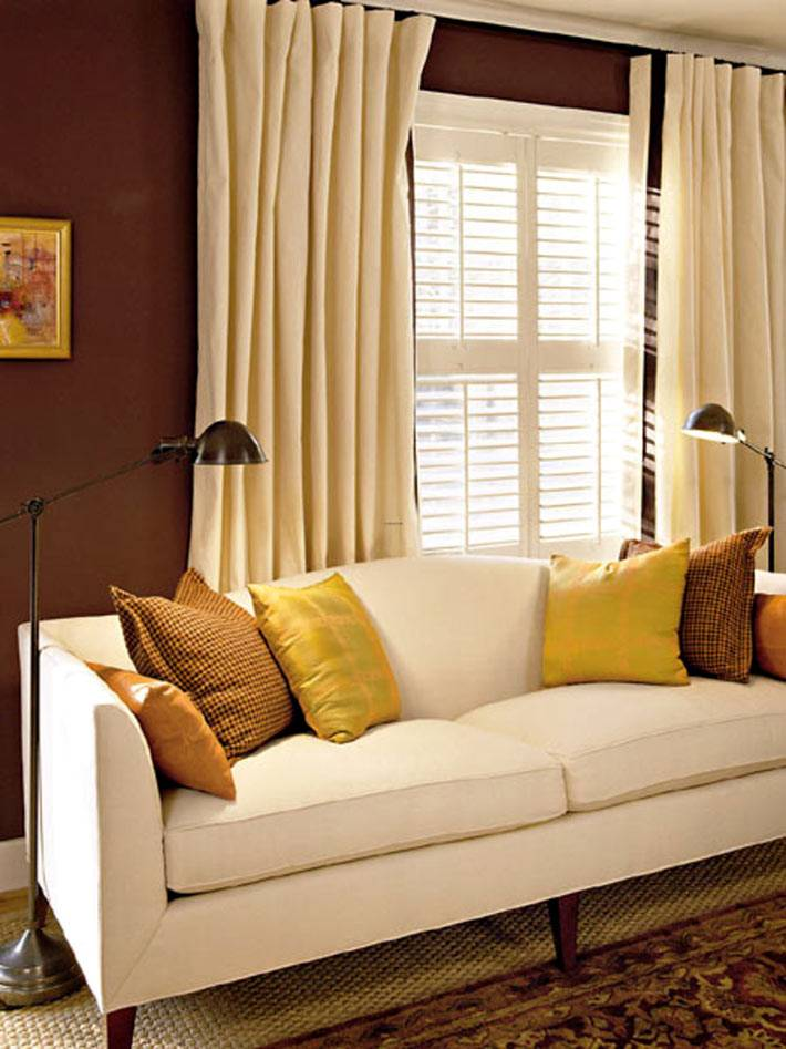 белый диван в интерьере комнаты коричневого цвета