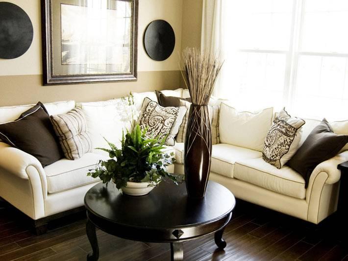 белый угловой диван и круглый черный журнальный стол