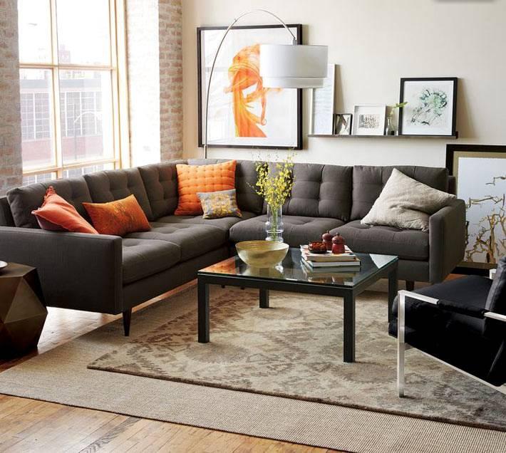 серый угловой диван на ножках в интерьере комнаты