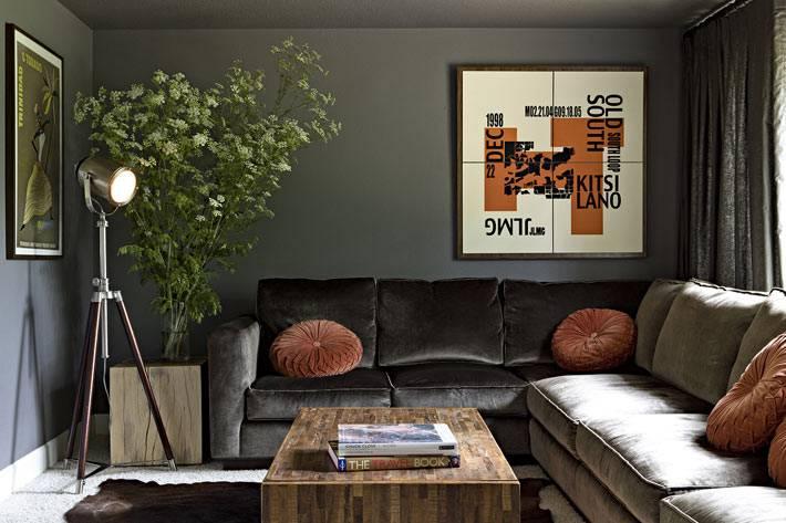 серый угловой диван в темной гостиной комнате