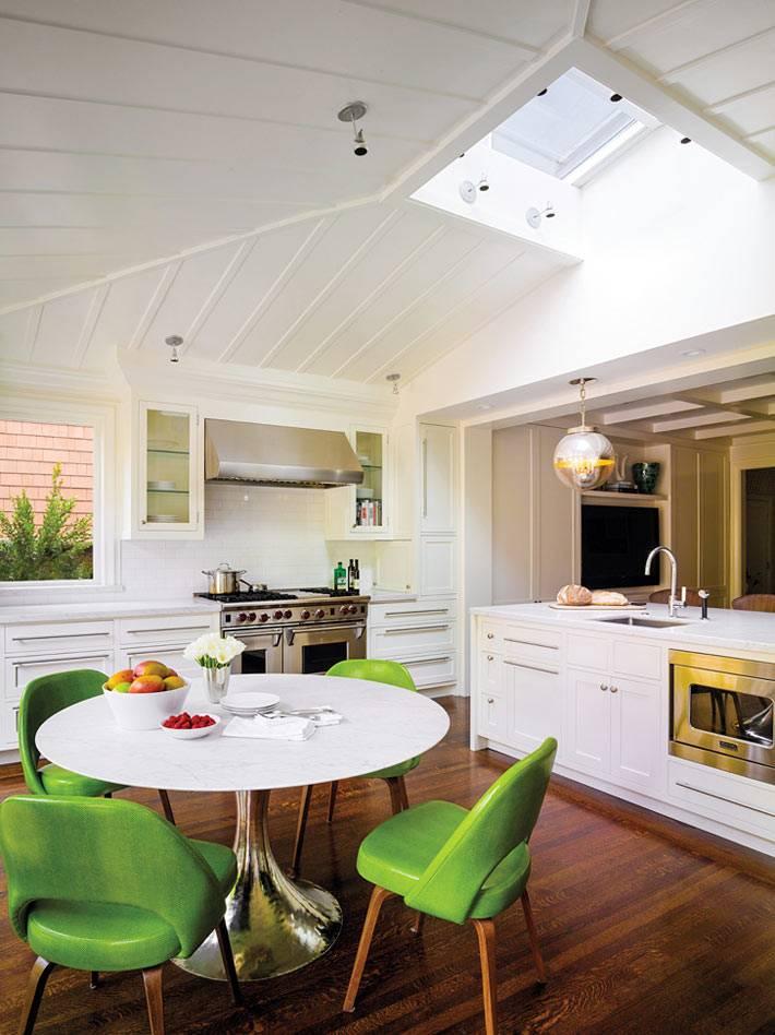 круглый стол и зеленые стулья в интерьере кухни