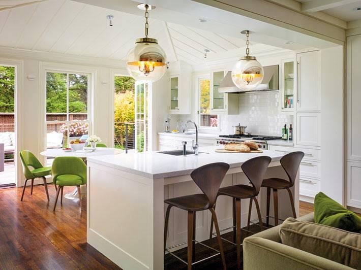 красивый интерьер белой кухни с островом в большом доме