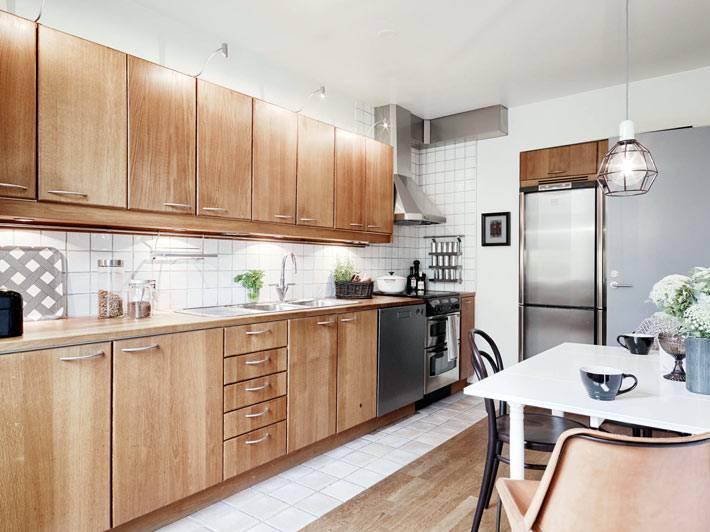 кухонный гарнитур из светлого дерева с белым фартуком