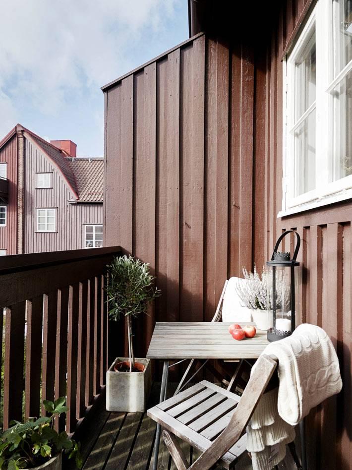 открытый балкон в квартире со столом и стулом