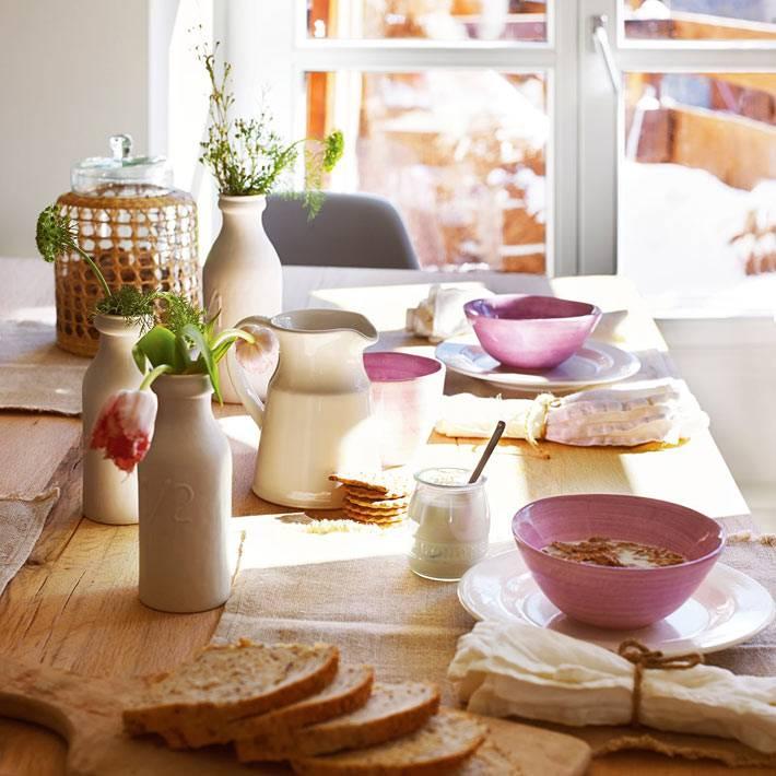 обеденный стол из массива дерева с красивой посудой в столовой