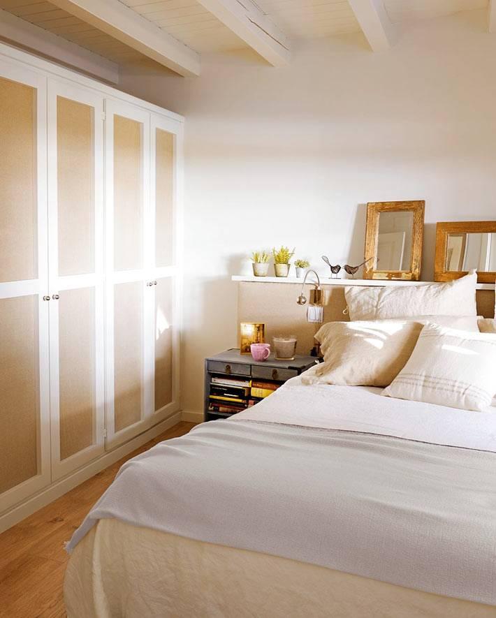 уютный интерьер спальни с большим белым шкафом для одежды