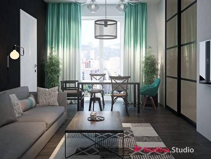 темный интерьер гостиной с зелеными шторами