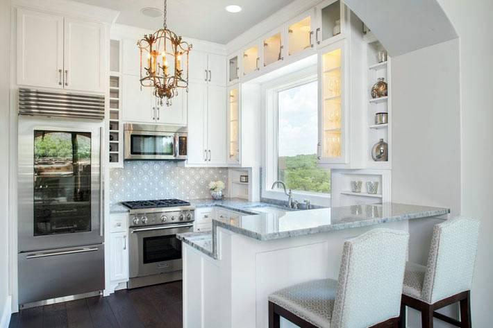 красивый белый интерьер кухни с мраморной столешницей