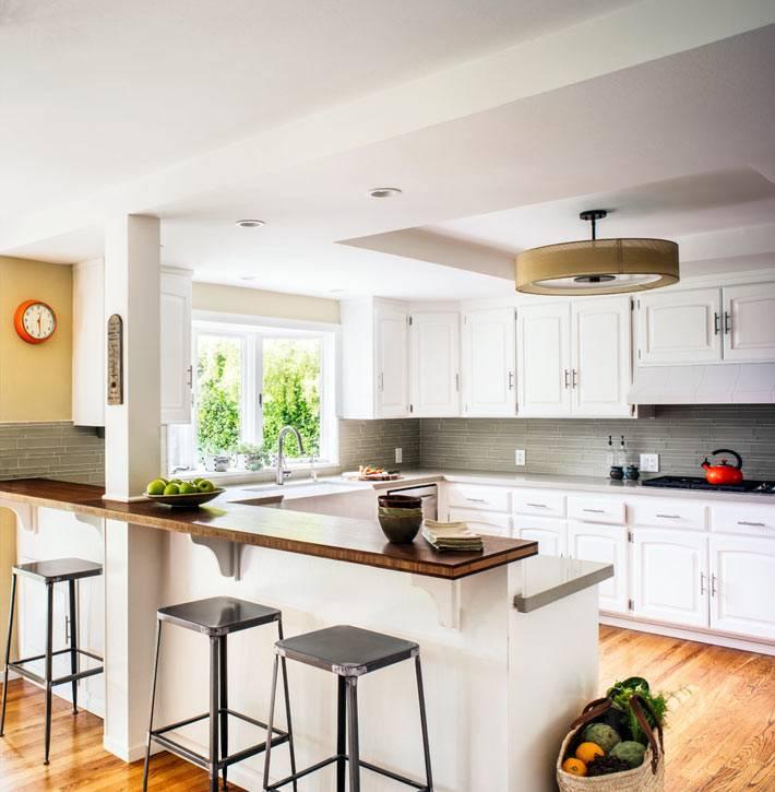 большой интерьер кухни в белом цвете с барной стойкой