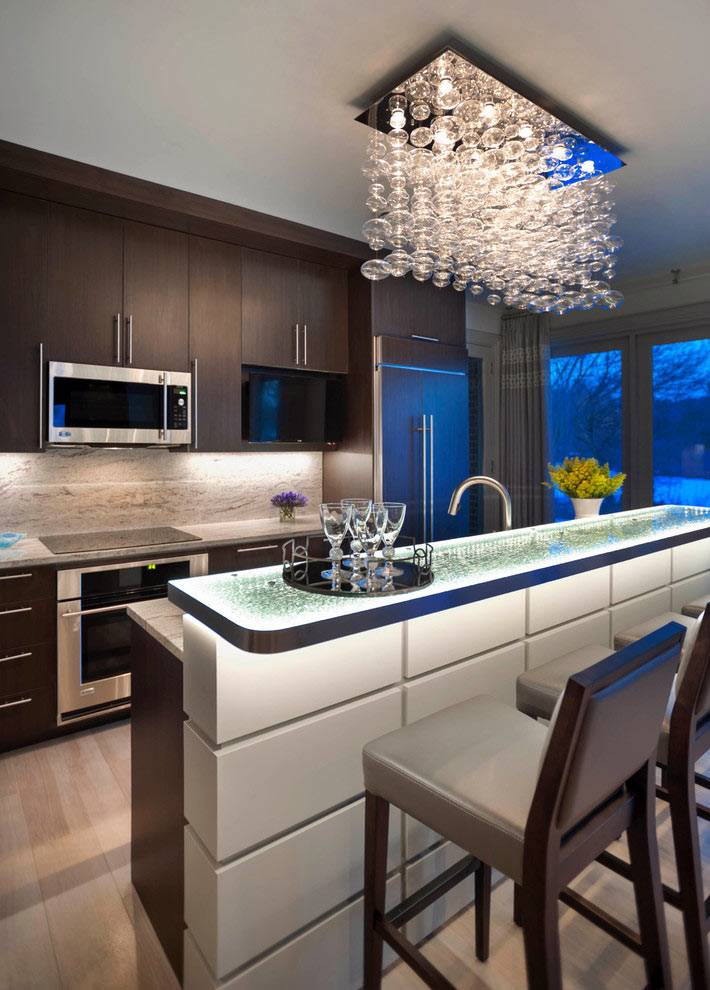 стеклянная барная стойка и хрустальная люстра в интерьере кухни