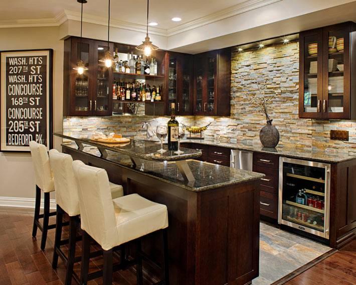 красивая коричневая кухня с барной стойкой и белыми стульями