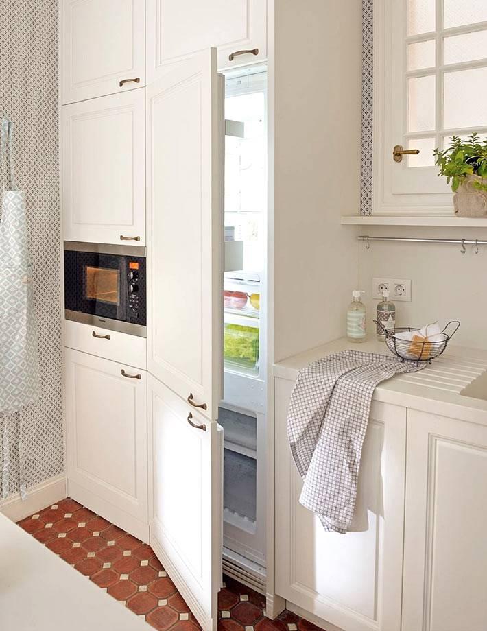 встроенный холодильник за белым фасадом на кухне