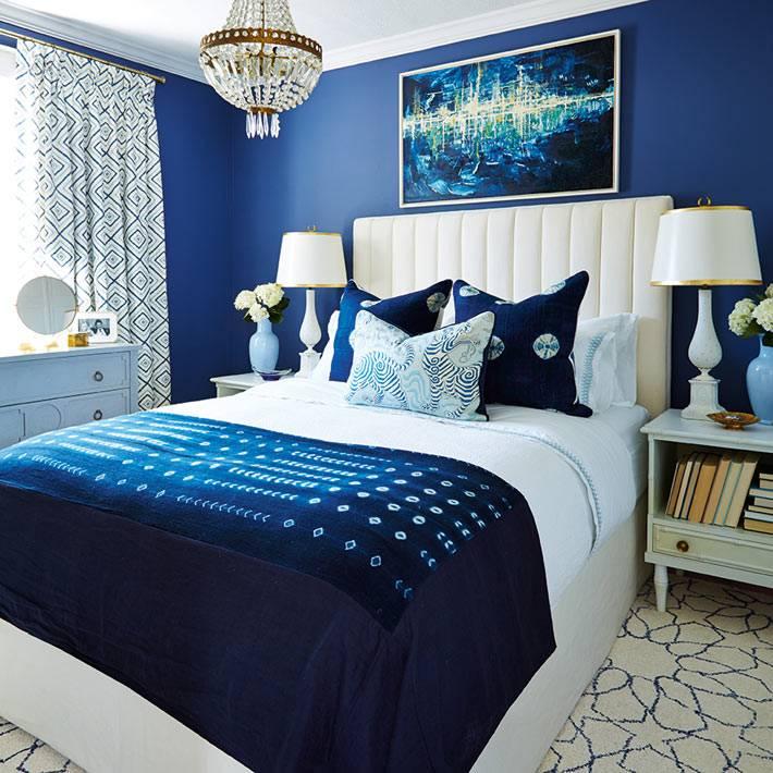 белая кровать в спальной комнате с синими стенами