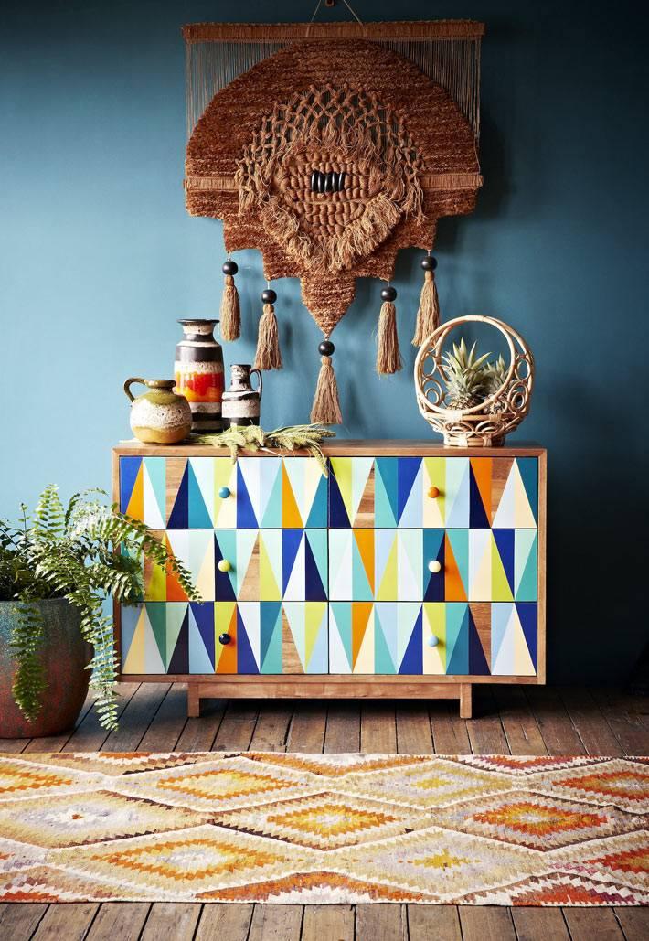 яркий комод с пестрым рисунком возле синей стены фото