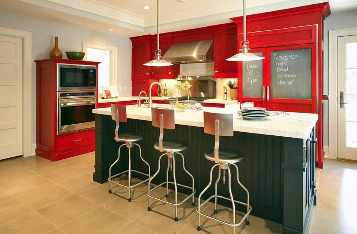 красная кухонная мебель с темно-зеленым островом