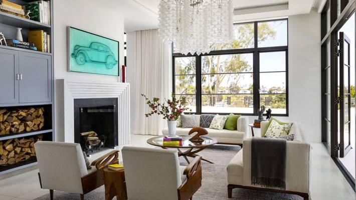 большое окно во всю стену и камин в красивой гостиной