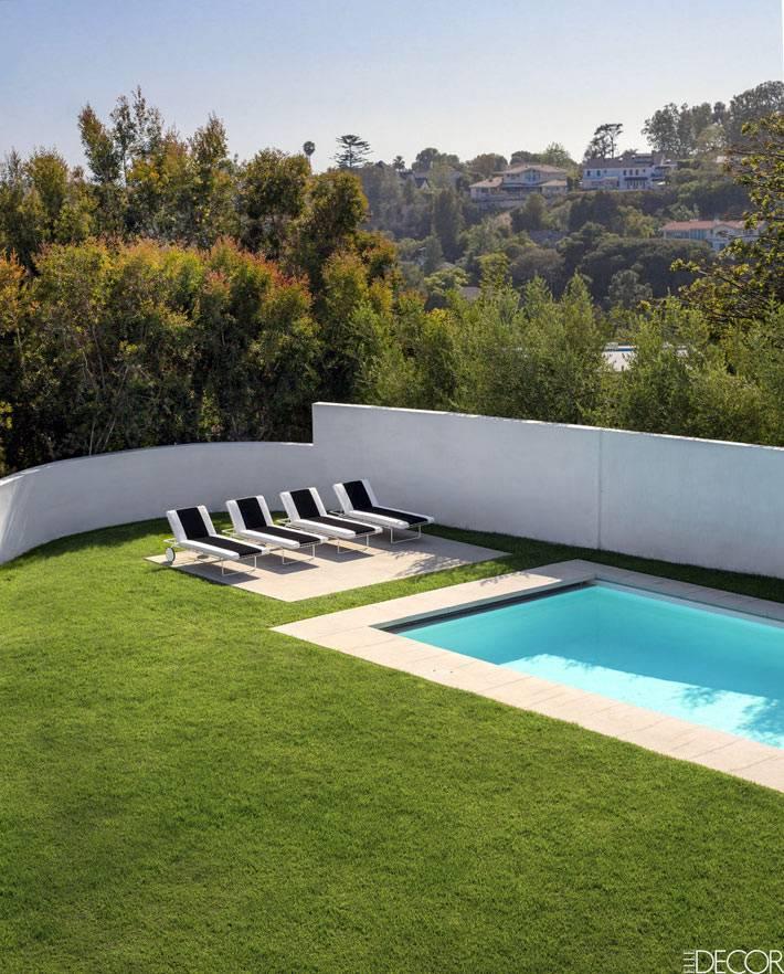 красивый двор с лужайкой и бассейном возле дома