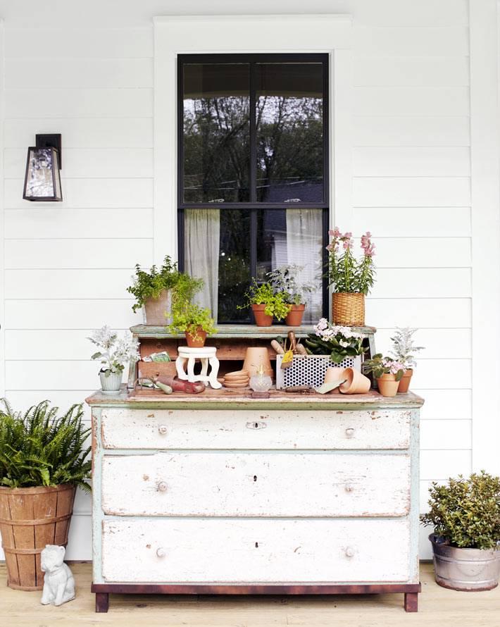 старый комод на крыльце дома для цветочных горшков