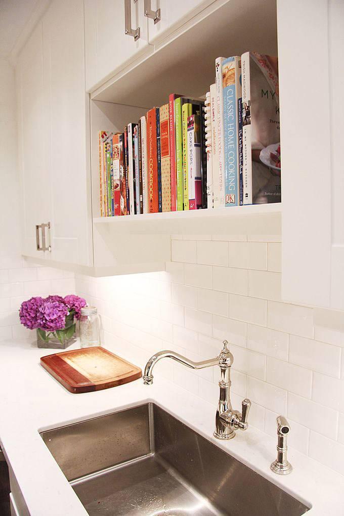 кулинарные книги на кухонном гарнитуре над раковиной