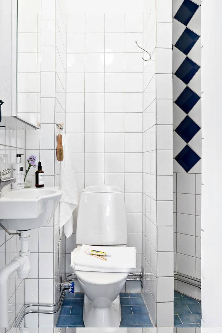 санузел маленькой квартиры облицован простой белой плиткой