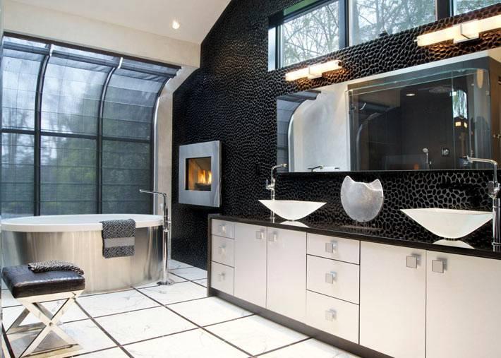 большая ванная комната с камином с черными стенами и белой сантехникой