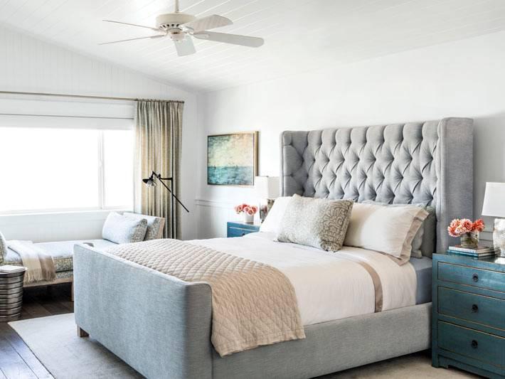 серая кровать и высоким мягким изголовьем в спальне