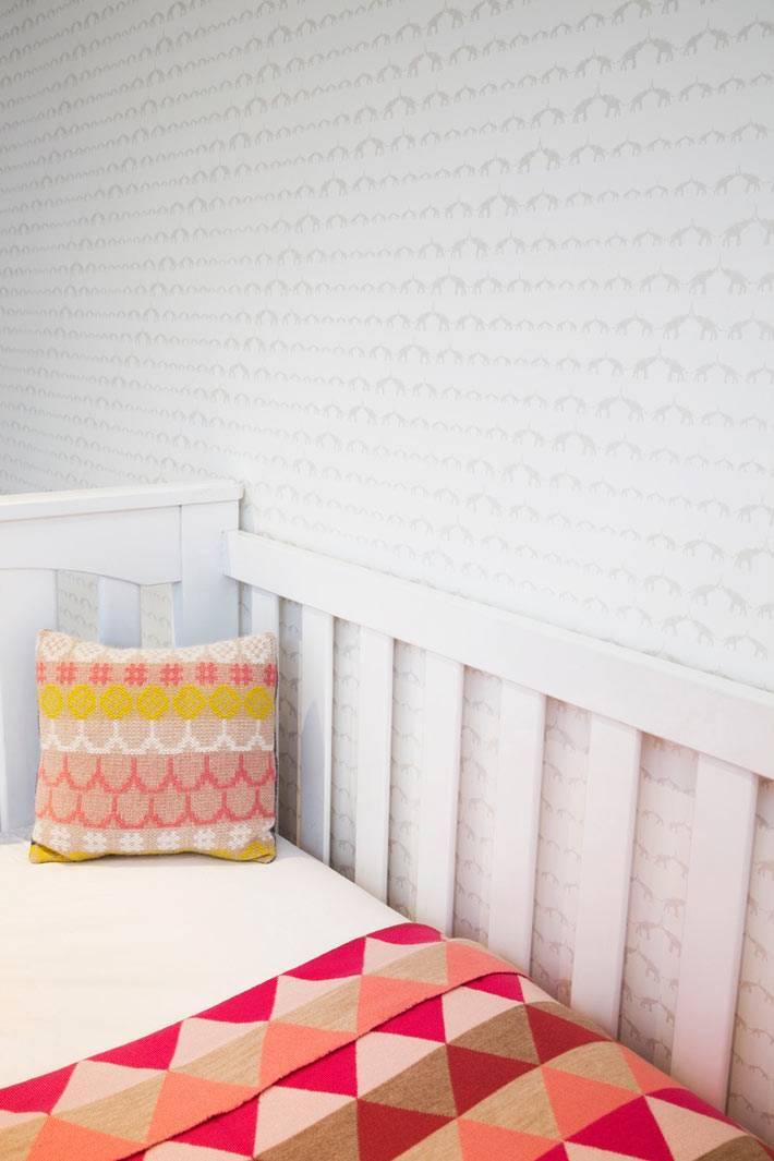 яркая постель для младенцев в белом интерьере детской фото