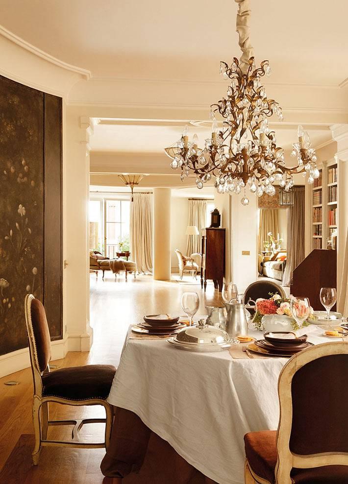 красивый дизайн столовой комнаты с хрустальной люстрой над столом