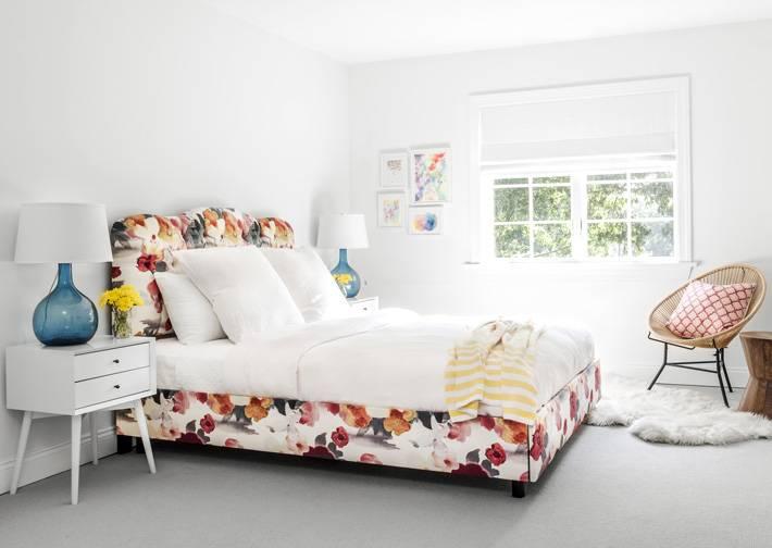 интерьер спальни с цветастой кроватью и белыми стенами