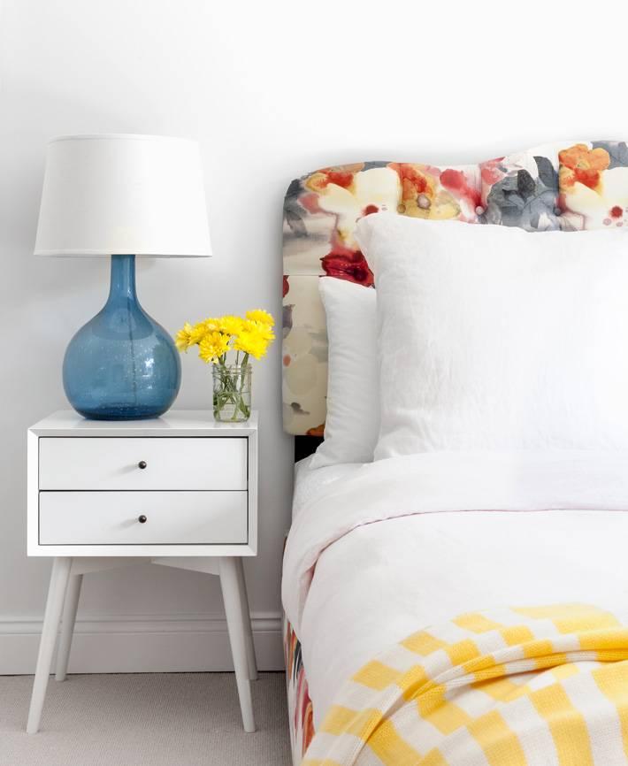 яркое изголовье кровати в цветах и белая мебель для спальни