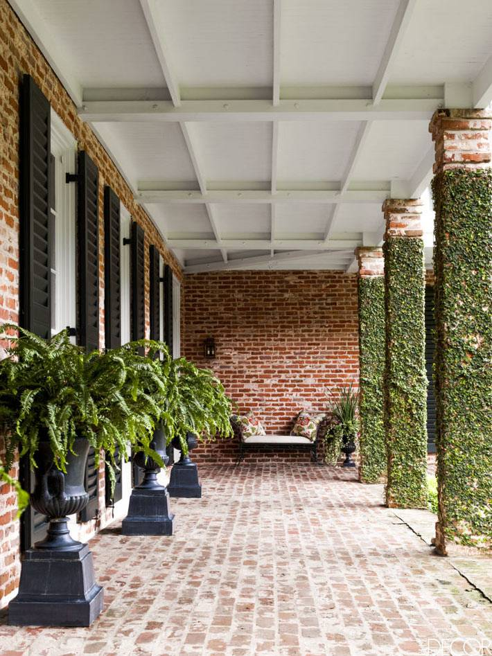 красивый дом с коланнами в Хьюстоне с папоротниками на террасе