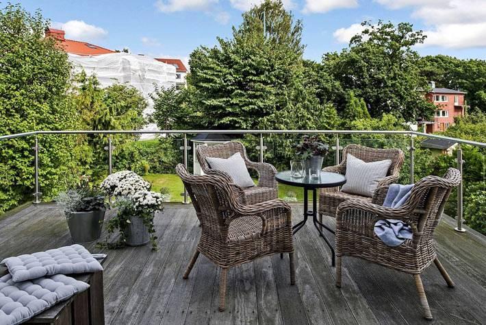 большая терраса с плетеной мебелью в загородном доме